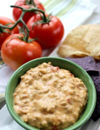 Crock-Pot Mexican dip in a green bowl with tortilla chips and tomatoes on the side