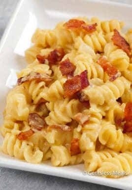Beer macaroni and cheese on a white plate with bacon