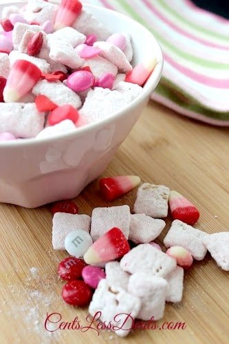 Strawberry Muddy Buddies recipe with some in a bowl and some on a wooden board