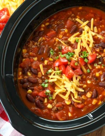 Crock-Pot taco chili in a crock pot topped with shredded cheese tomatoes and green onions