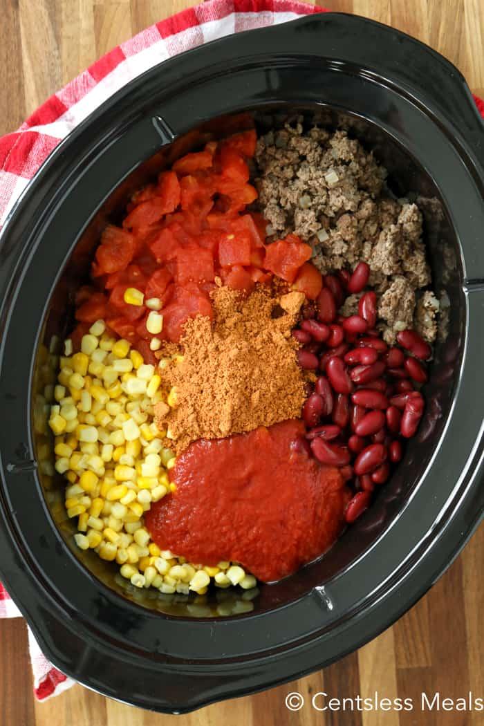 Crock pot taco chili ingredients in a black Crock-Pot
