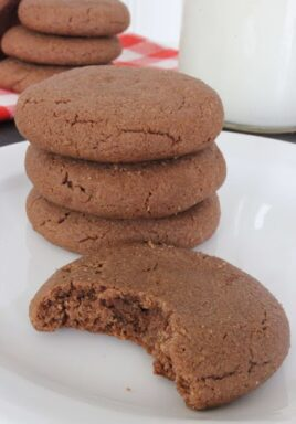 Four ingredient chocolate peanut butter cookies on a plate with a bite taken out of 1