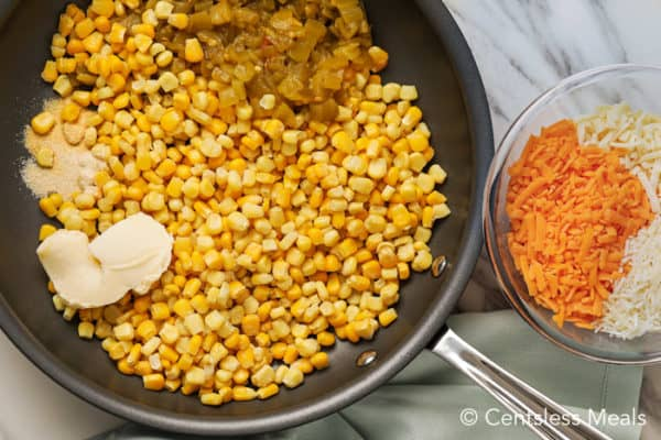 Ingredients for corn casserole in a frying pan and in a glass bowl on a marble board