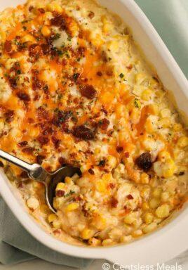 Corn casserole in a white casserole dish with a spoon