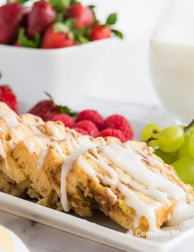 Crock-Pot cinnamon buns with icing and fruit on the side on a white plate