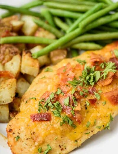 Parmesan crusted chicken on a plate with potatoes and green beans