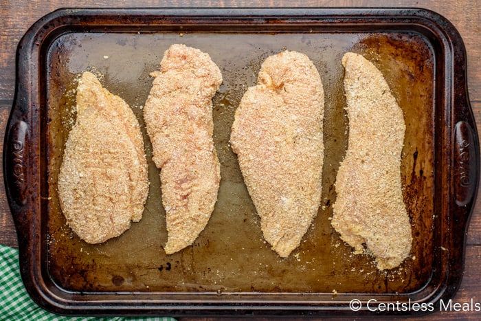 Coated chicken on a baking sheet
