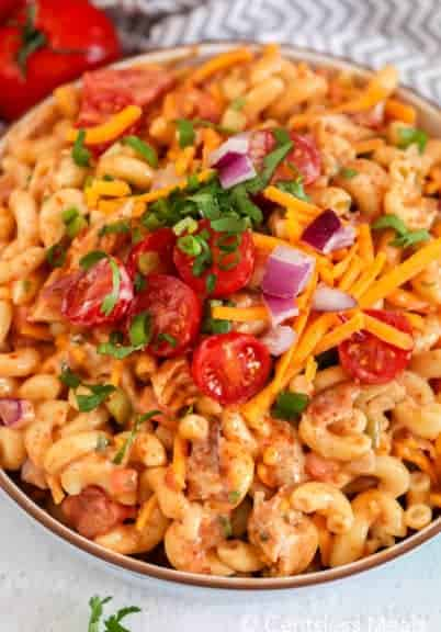 Barbecue chicken macaroni salad in a bowl garnished with tomatoes cheese and onion