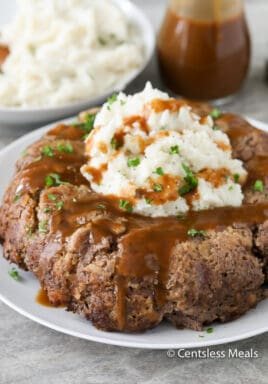 Stove top meatloaf on a plate with mashed potatoes gravy and parsley