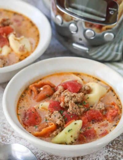 Creamy tomato tortellini soup in white bowls garnished with parsley