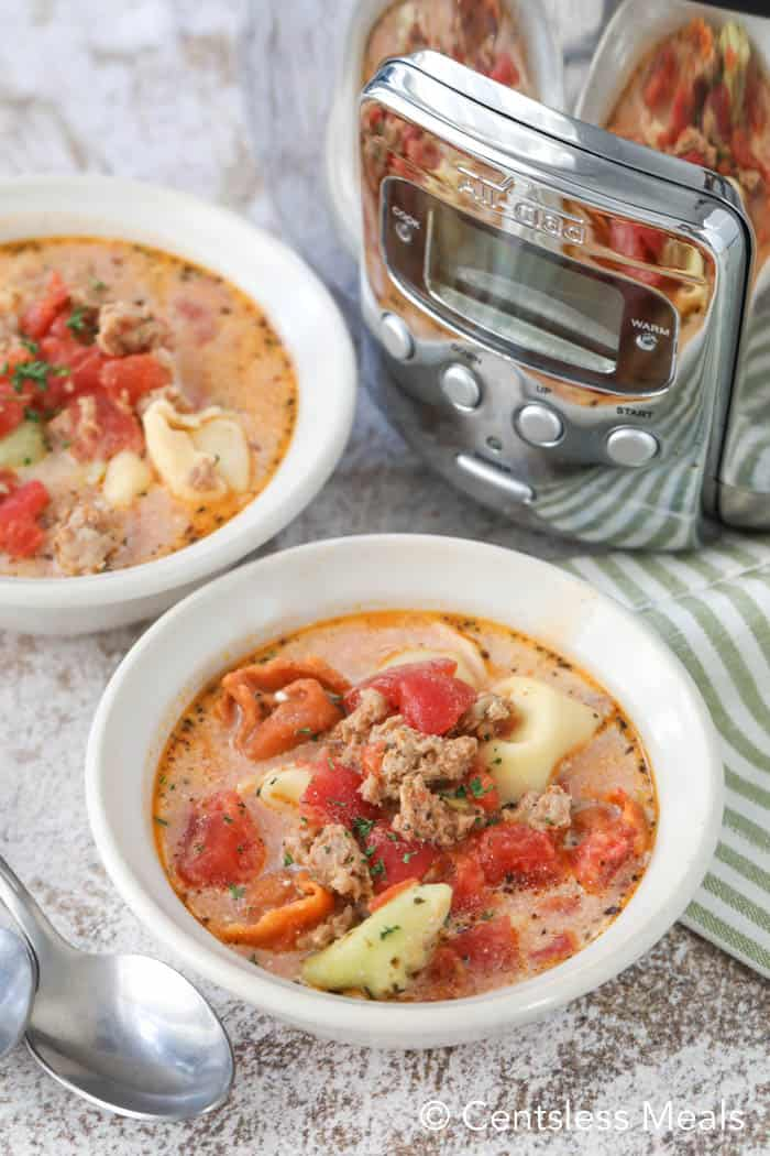 Creamy tomato tortellini soup in white bowls with a Crock-Pot in the background