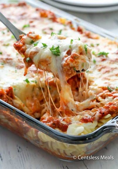 Sour cream noodle bake in a casserole dish with a scoop being taken out with a serving spoon