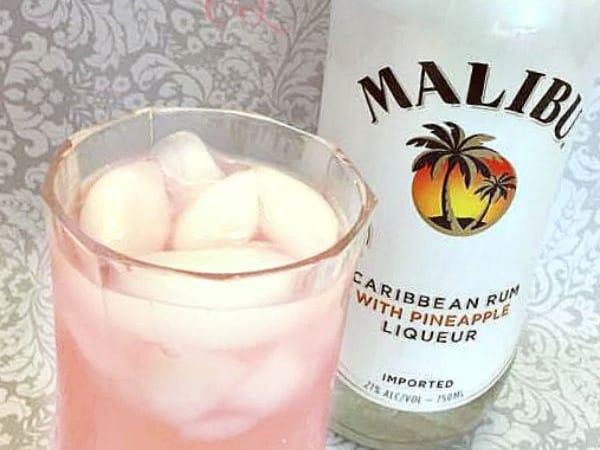 Bottle of Malibu liqueur next to a glass of sassy lemonade