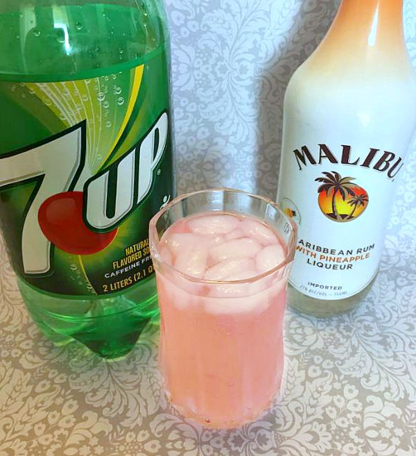 Bottle of 7up and Malibu liqour, with glass of sassy lemonade in between them