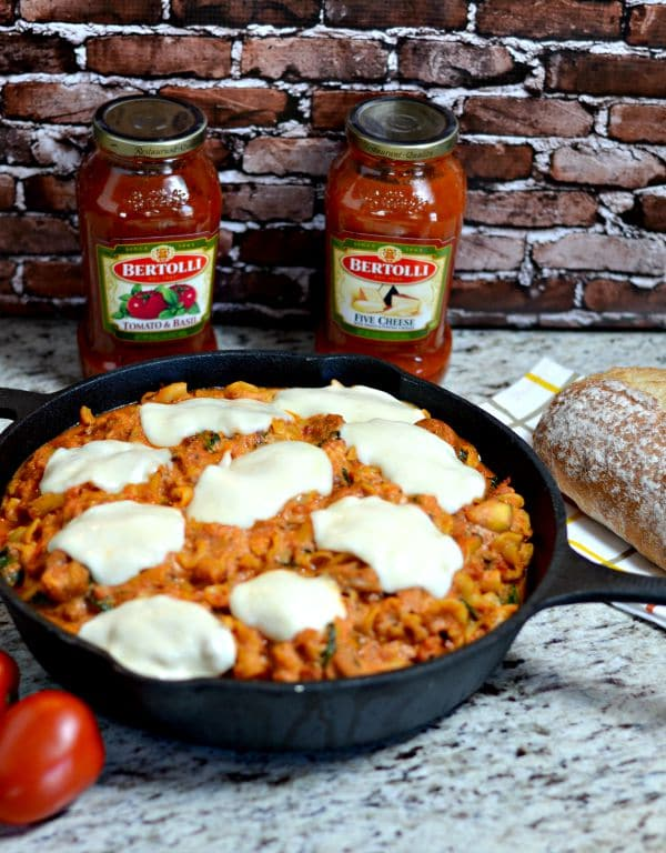Tuscan Pasta in a skillet with two jars of Bertolli pasta sauce in the background
