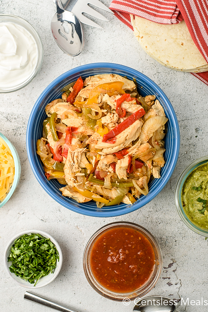 Crock-Pot chicken fajitas in a blue bowl with salsa guacamole cilantro cheese and sour cream on the side