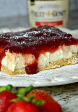 Strawberry cheesecake bar on a white plate with strawberries and jam in the background