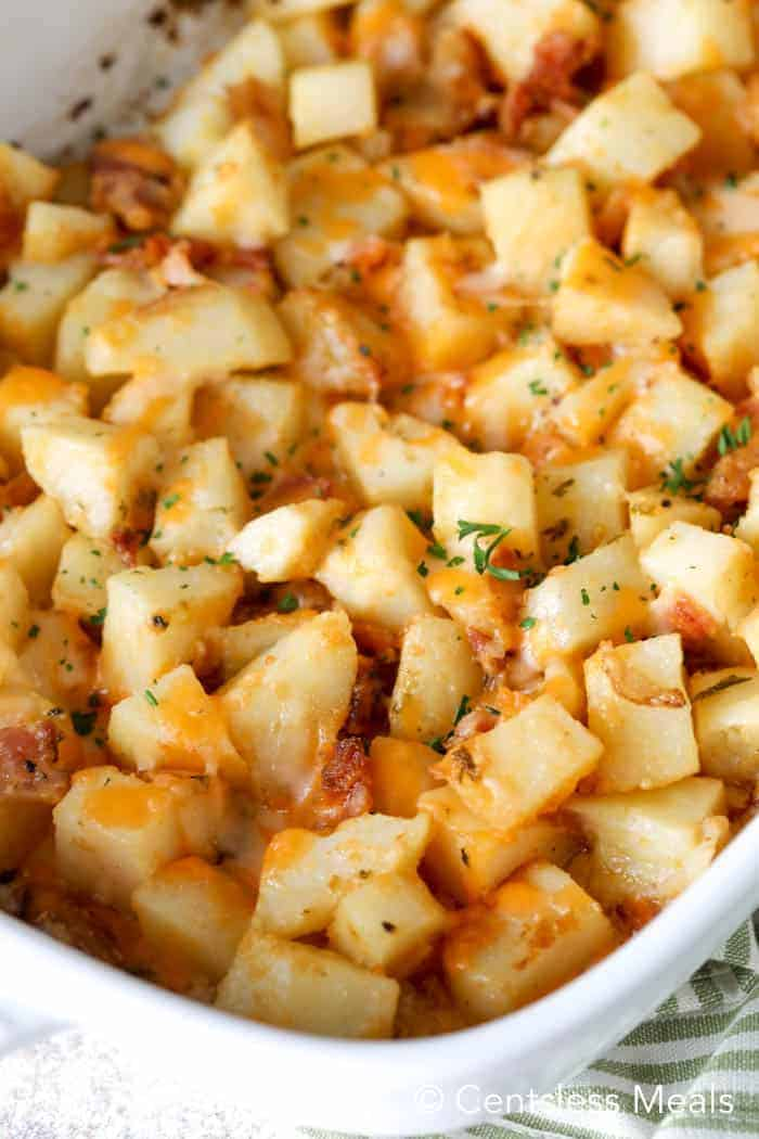 Close up of cheesy ranch potatoes baked in a white casserole dish.
