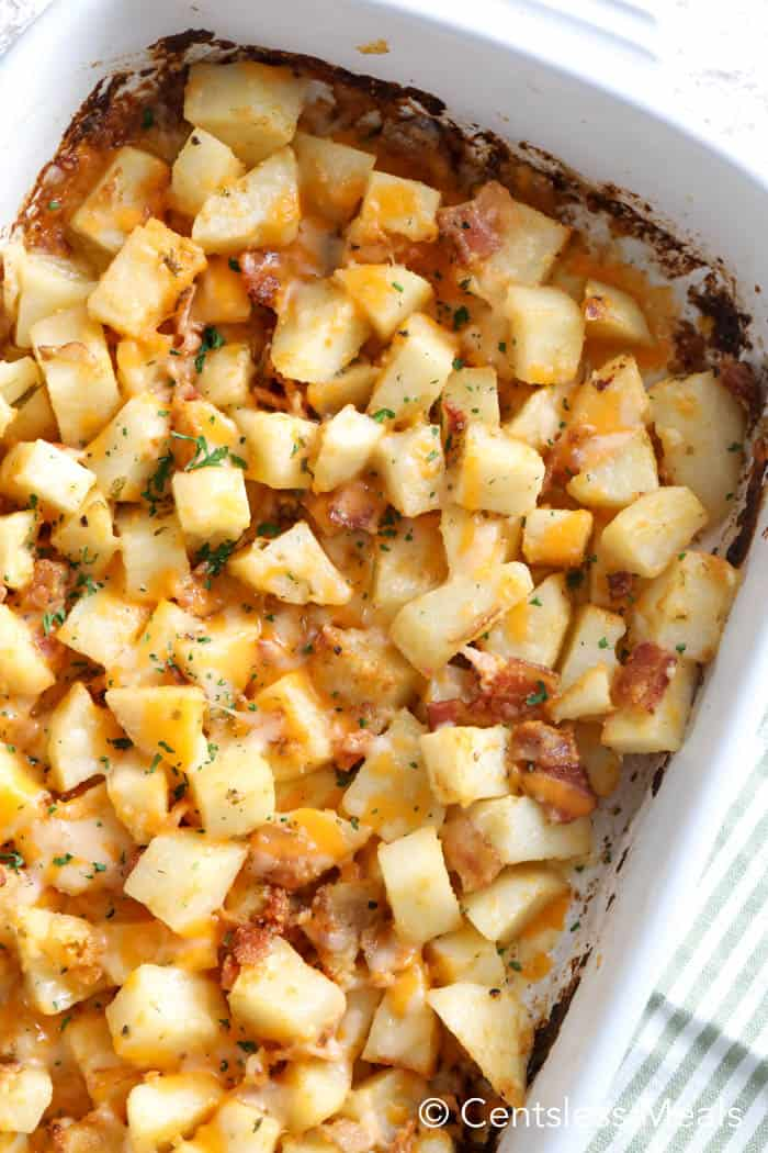 A cheesy baked potato casserole garnished with parsley.