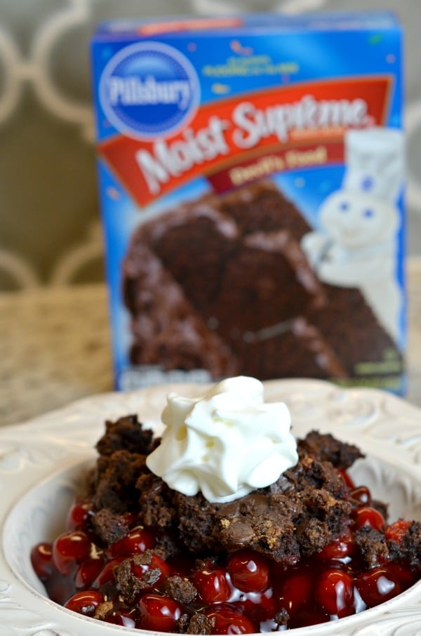 Chocolate cherry dump cake recipe in a bowl topped with whipped cream and Pillsbury black forest cake in the background