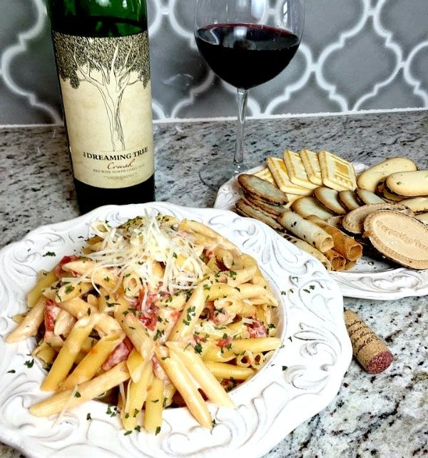 Creamy one pot pasta with a plate of cookies and a glass of wine