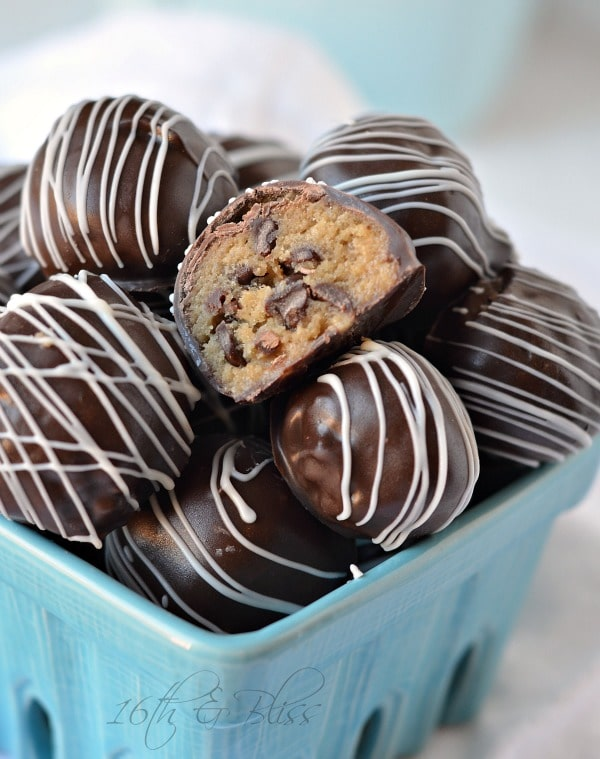 Chocolate chip cookie dough truffles in a dish with 1 cut in half