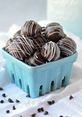 Chocolate chip cookie dough truffles in a dish drizzled with white chocolate