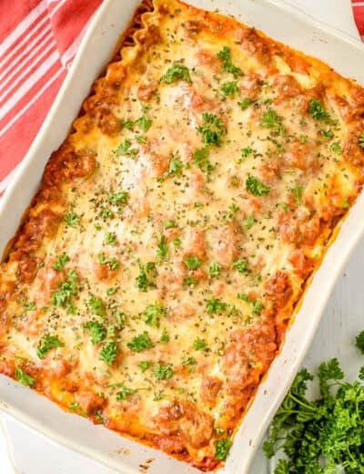 Cream cheese lasagna in a white casserole dish with parsley