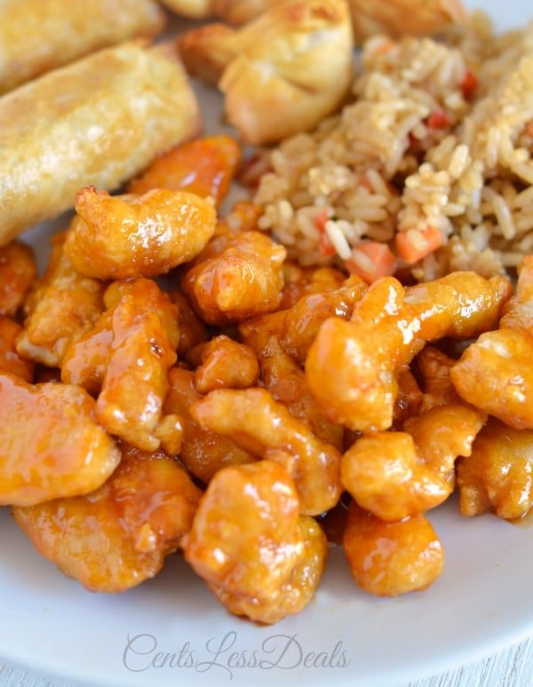 Orange chicken on a plate with rice and spring rolls