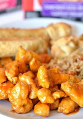 Easy orange chicken on a plate with rice and spring rolls