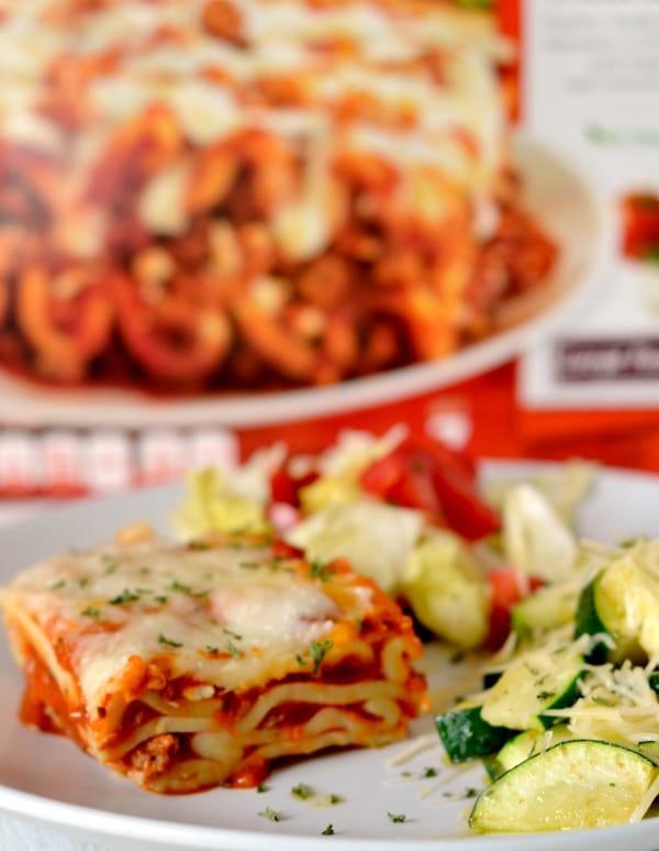 Easy parmesan zucchini on a white plate with lasagna