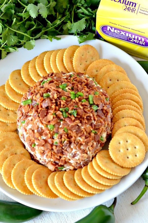 Bacon jalapeno cheese ball on a plate with crackers and heartburn medication