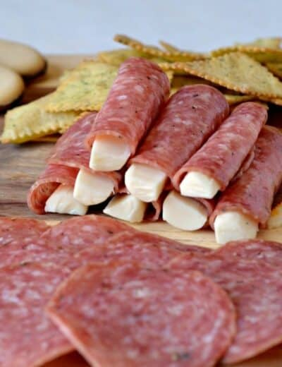 Meat cheese and crackers on a wooden board with some cheese wrapped in salami