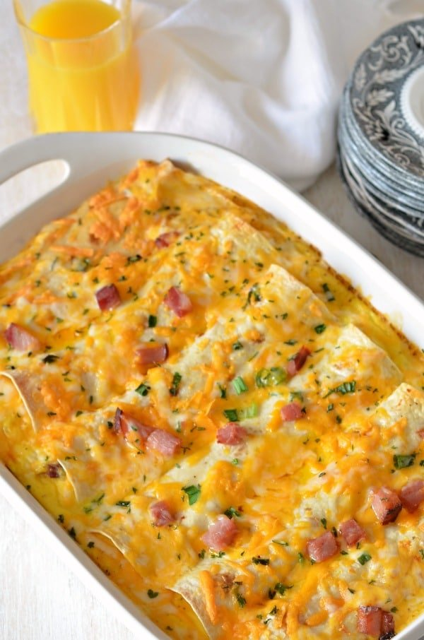 Overnight breakfast enchiladas in a white casserole dish with plates and a glass of orange juice