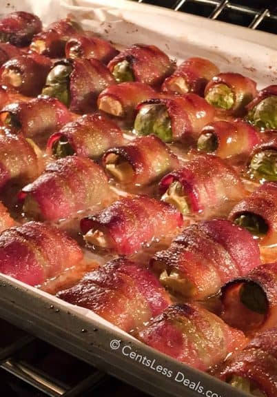 Bacon wrapped brussel sprouts on a baking sheet in the oven