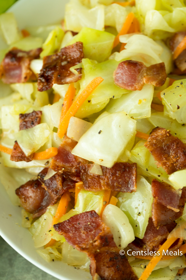 Fried cabbage and bacon in a white bowl