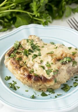 Oven baked pork chop on a blue plate with parsley on top