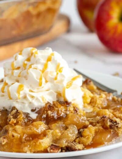 Caramel apple dump cake on a white plate with whipped cream on top