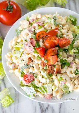 BLT pasta salad in a white bowl with tomatoes on top