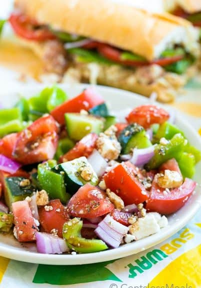 Easy Greek salad on a white plate with a Subway sandwich in the background