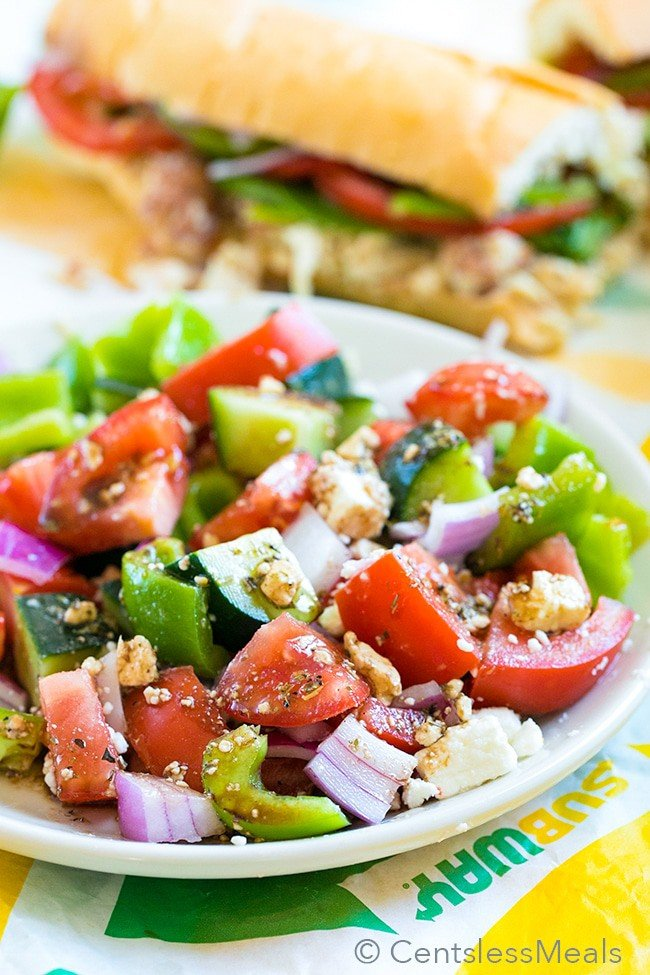 An easy Greek Salad loaded with ripe juicy tomatoes, crisp cucumbers and creamy feta cheese all tossed in a simple homemade dressing. This is the perfect dish to serve alongside a tender rotisserie chicken sub for the perfect summer meal.