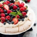 Pavlova topped with berries on a white plate with berries garnished with mint leaves.