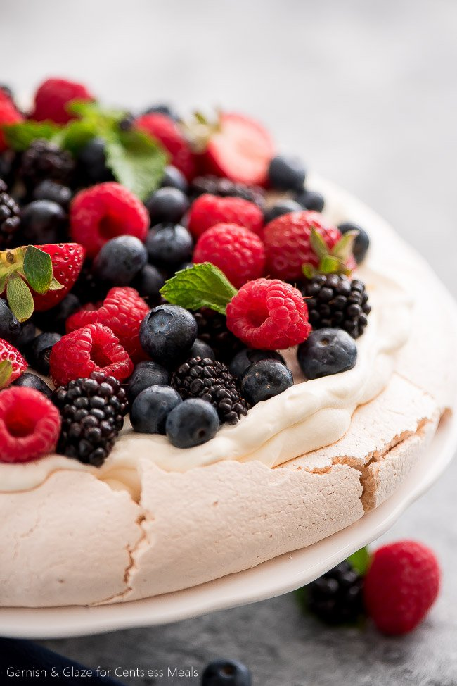 For a simple, beautiful, and refreshing dessert this summer, make this Berry Topped Pavlova! Fresh berries and whipped cream top a delicate meringue cloud to create the most heavenly dessert imaginable!