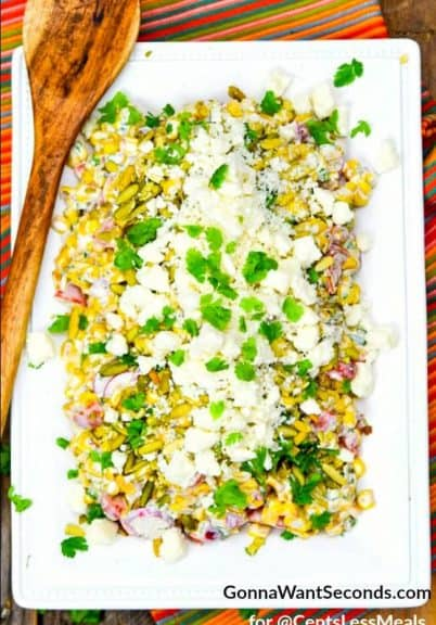 Mexican Corn Salad on a white serving plate with cilantro and a wooden spoon