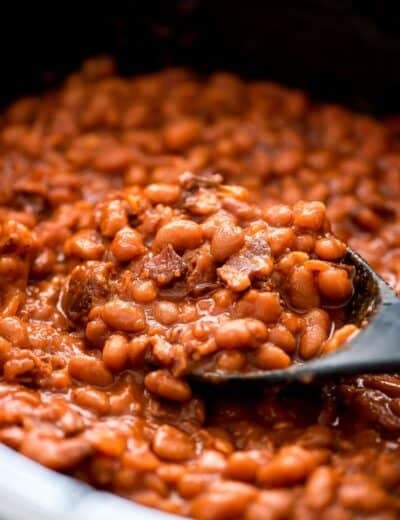 Crock-Pot baked beans being scooped up with a spoon