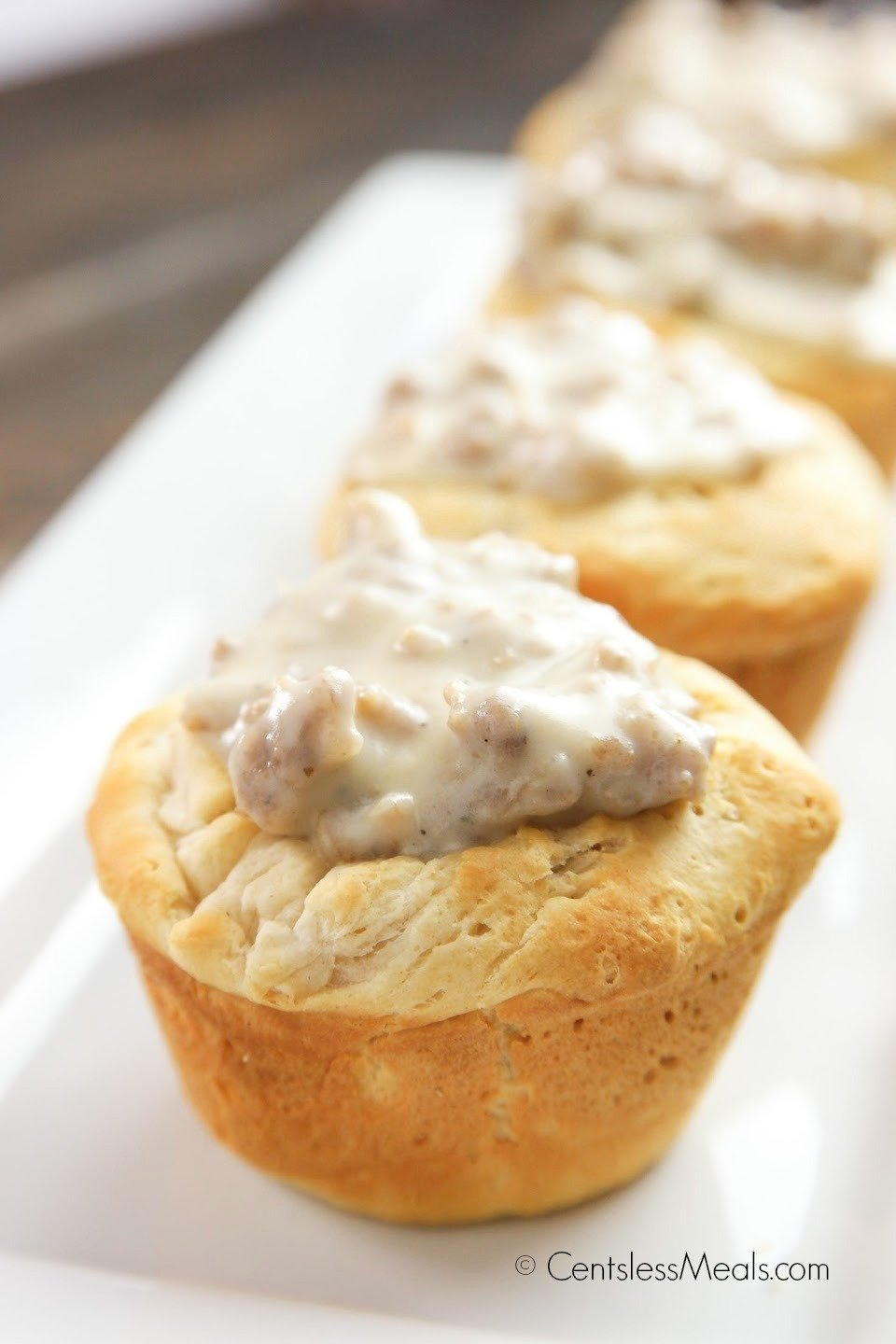 Biscuit and gravy cups on a white serving plate with gravy on top of the biscuit