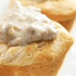 Biscuits and gravy cups on a white plate with gravy on top