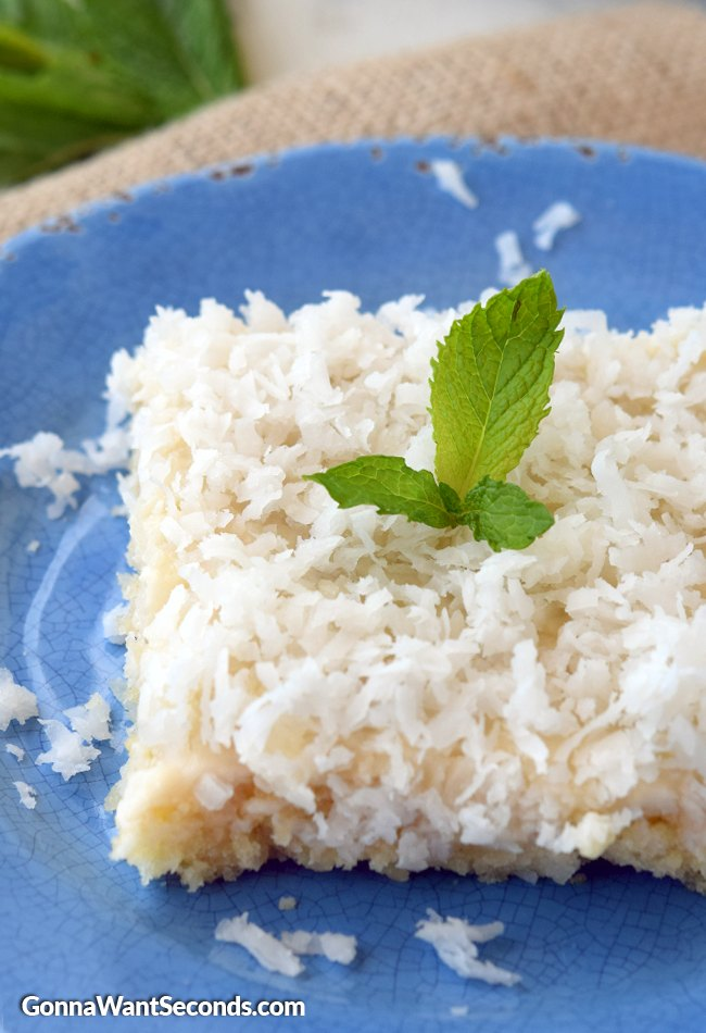 Coconut Sheet Cake on a blue plate with a mint leaf