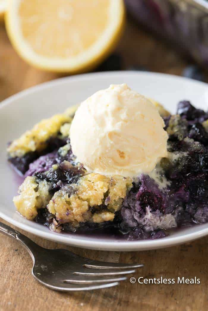 Lemon blueberry dump cake on a white plate with a scoop of ice cream and a fork