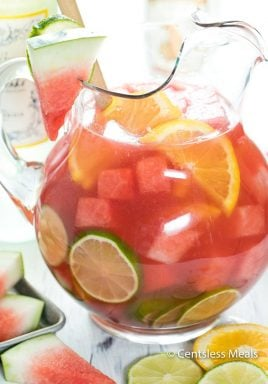 Watermelon sangria in a glass pitcher garnished with watermelon lime and lemon